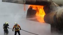 De brandweermannen & vrouw blusten de motor